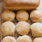 Birds eye view of 9 wholemeal rolls and a loaf of wholemeal bread on a baking rack.