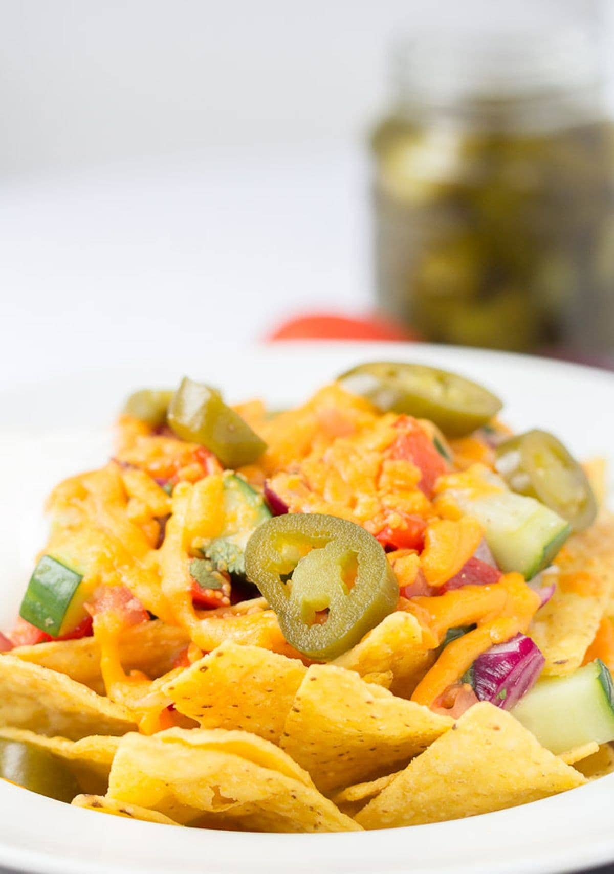 A plate of nachos with spicy salsa and melted cheese on top.