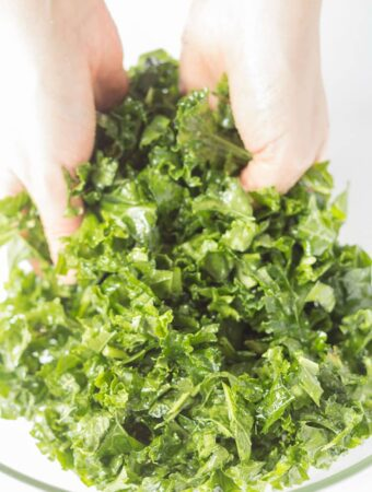 Hands massaging a bowl of curly kale crisps.