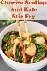 A bowl of chorizo scallop and kale stir fry with two chop sticks sticking up.