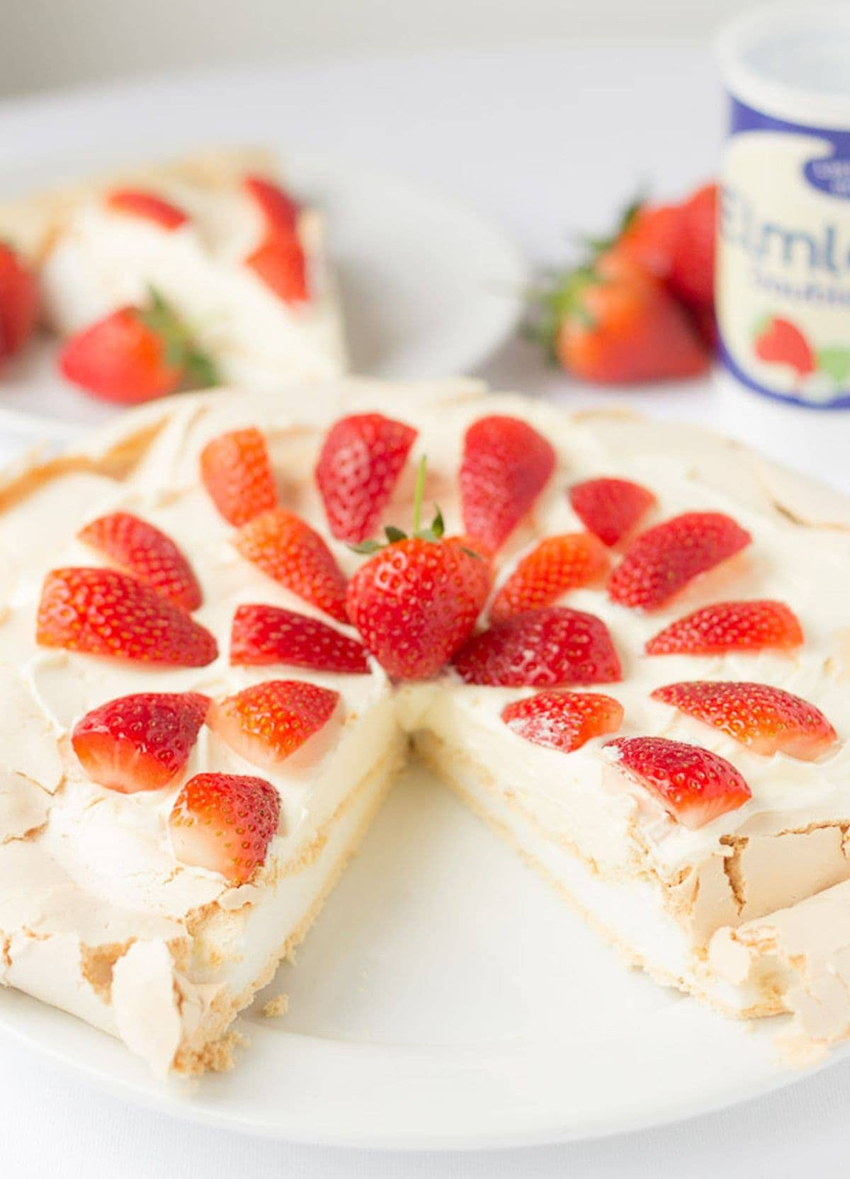 Strawberry Pavlova on a plate decorated with strawberry halves with a slice taken out.