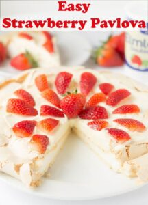 Easy strawberry pavlova decorated with sliced strawberries and a slice taken out.