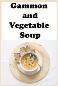 A bowl of ham and vegetable soup on a board with a spoon in it. Slices of bread around the board.