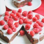 Low fat summer chocolate pudding cake decorated with icing sugar and raspberries on a plate with a slice taken out of it and placed on a side plate in the background.