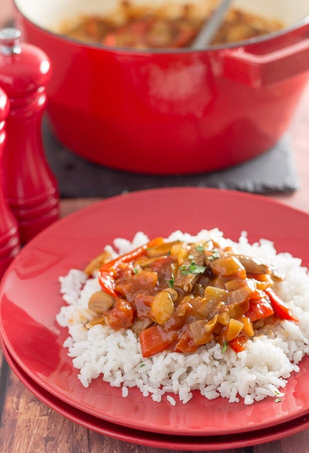 A plate of venison sausage casserole served on a portion of rice with the casserole pot in the background.