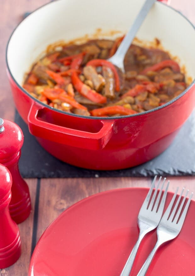 A pot of low fat venison sausage casserole sitting on a slate in front of a plate with 2 forks on it.