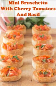10 slices of mini bruschetta with cherry tomatoes and basil on a bread board.