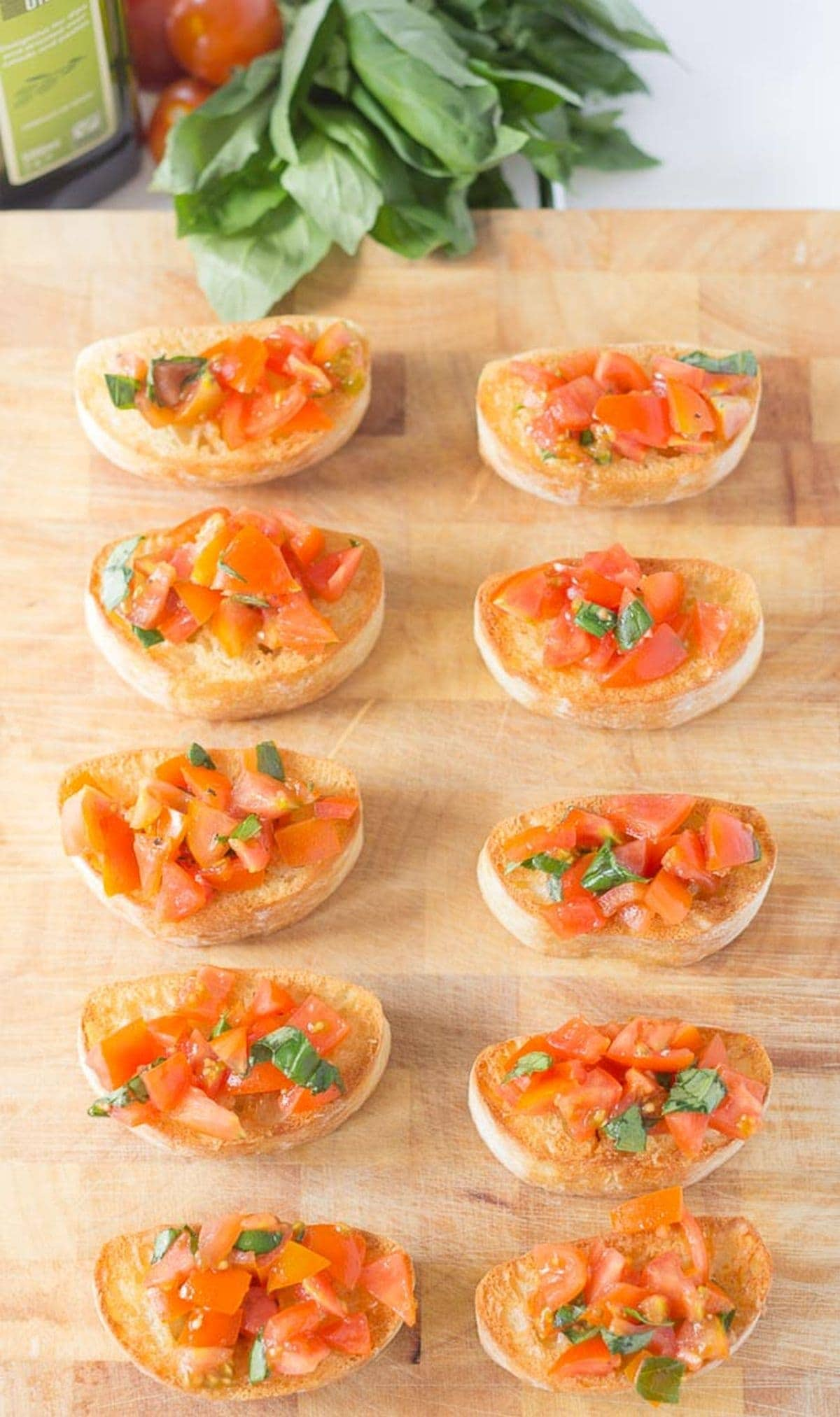 A bread board with 10 slices of mini bruschetta with cherry tomatoes and basil on.