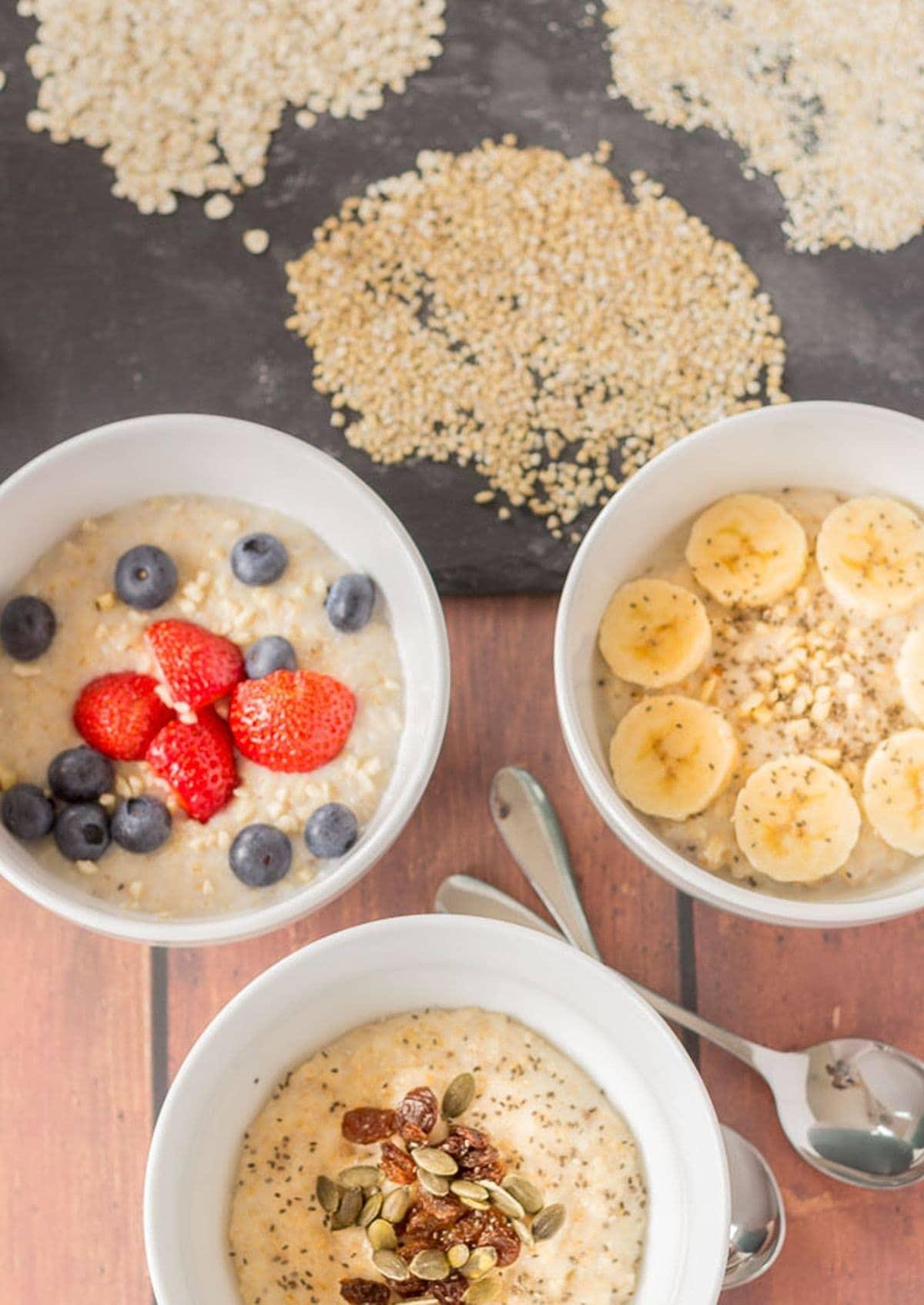 Birds eye view of 3 different types of cooked breakfast porridges. Porridge oats, oatmeal and pinhead oats.