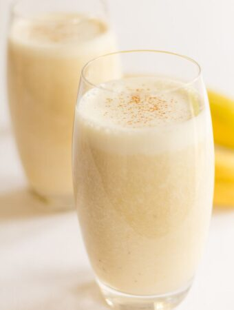 Two glasses of banana boost smoothie one in front of the other.