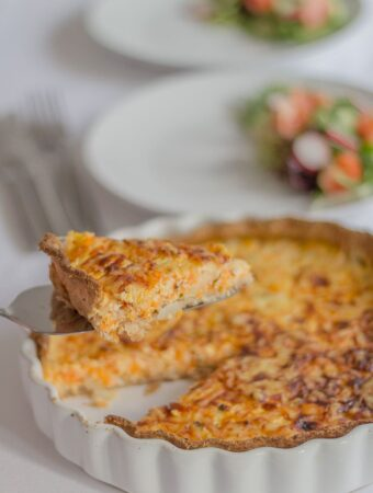 A slice of carrot and quark quiche being lifted out of a quiche dish.
