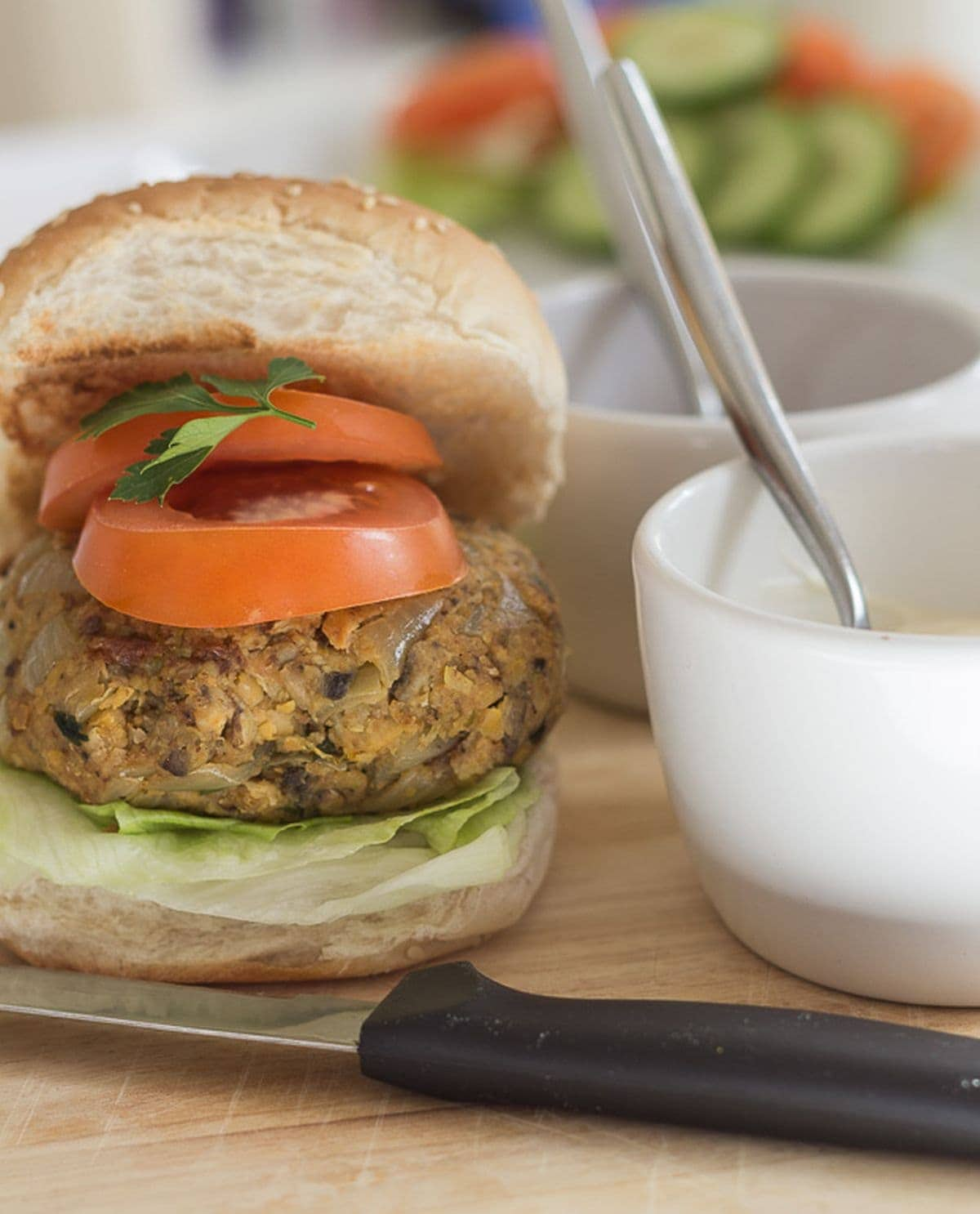A chickpea burger in a burger bun with sliced tomotoes on top. A small bowl of mayonnaise with a spoon in to the right.
