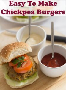 Birds eye view of a chickpea burger in a burger bun with sliced tomatoes on top. Mayonnaise and tomato ketchup in dishes to the side. Pin title at the top.