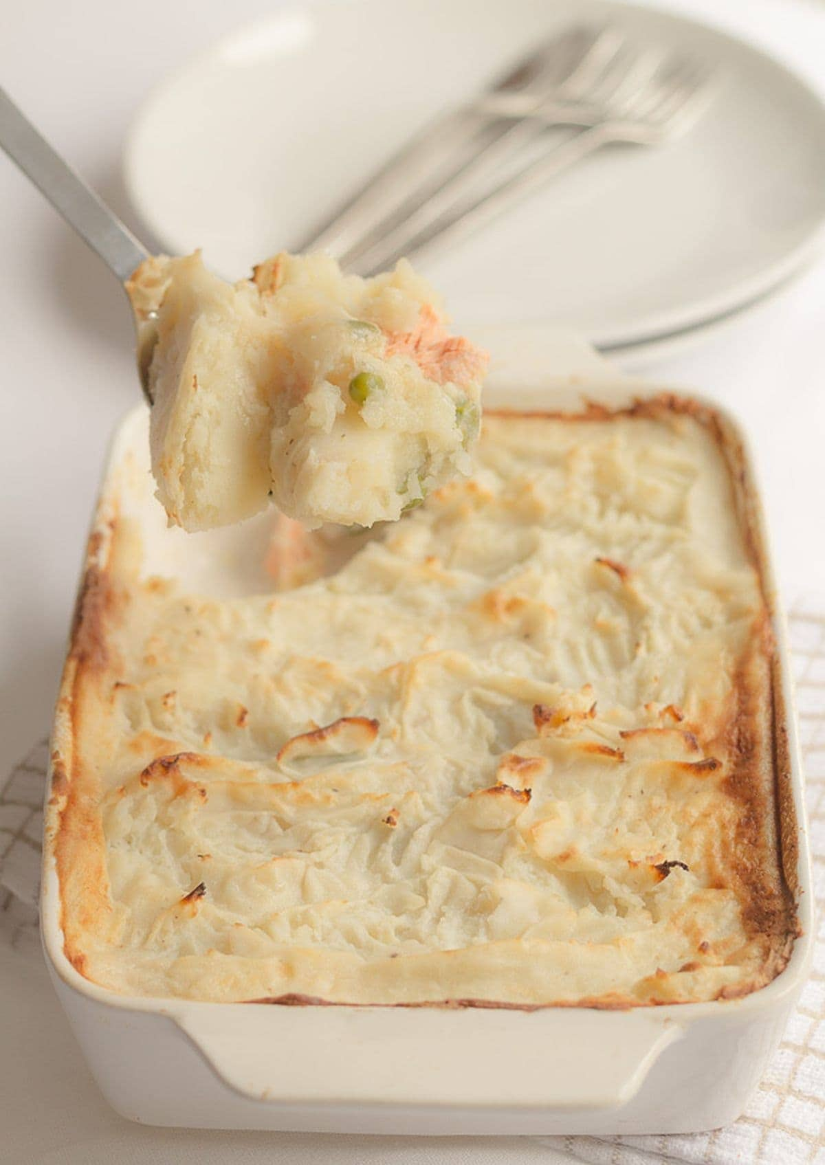 Easy fish pie just taken out of the oven with a spoon lifting a portion out.