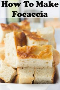 Rectangles of homemade Focaccia bread stacked on a serving plate.