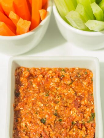 Low fat red pesto dip in a square dish with carrot and celery batons in the background.