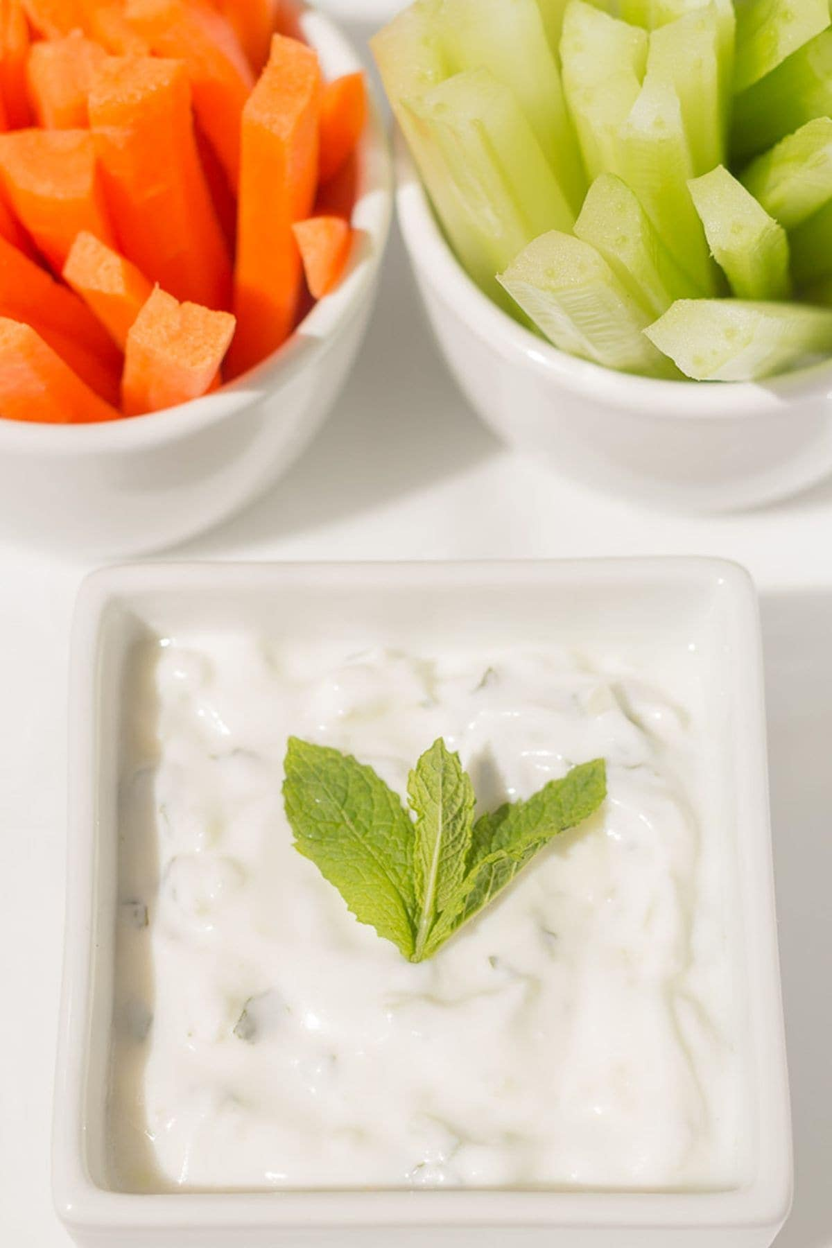 Low fat tzatziki dip in a small square serving dish with a sprig of mint leaves on top and crudities in the background.