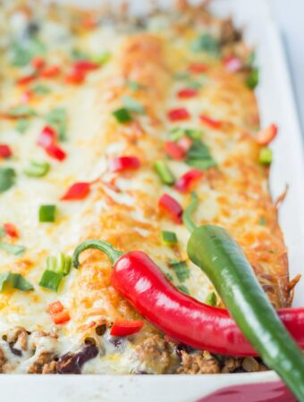 Cooked meat free quorn enchiladas in a casserole dish covered in melted cheese.