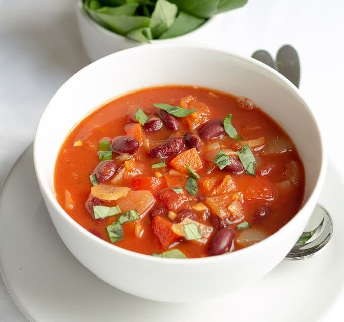 Close up view of the bowl of red pepper tomato and kidney bean soup looking delicious.