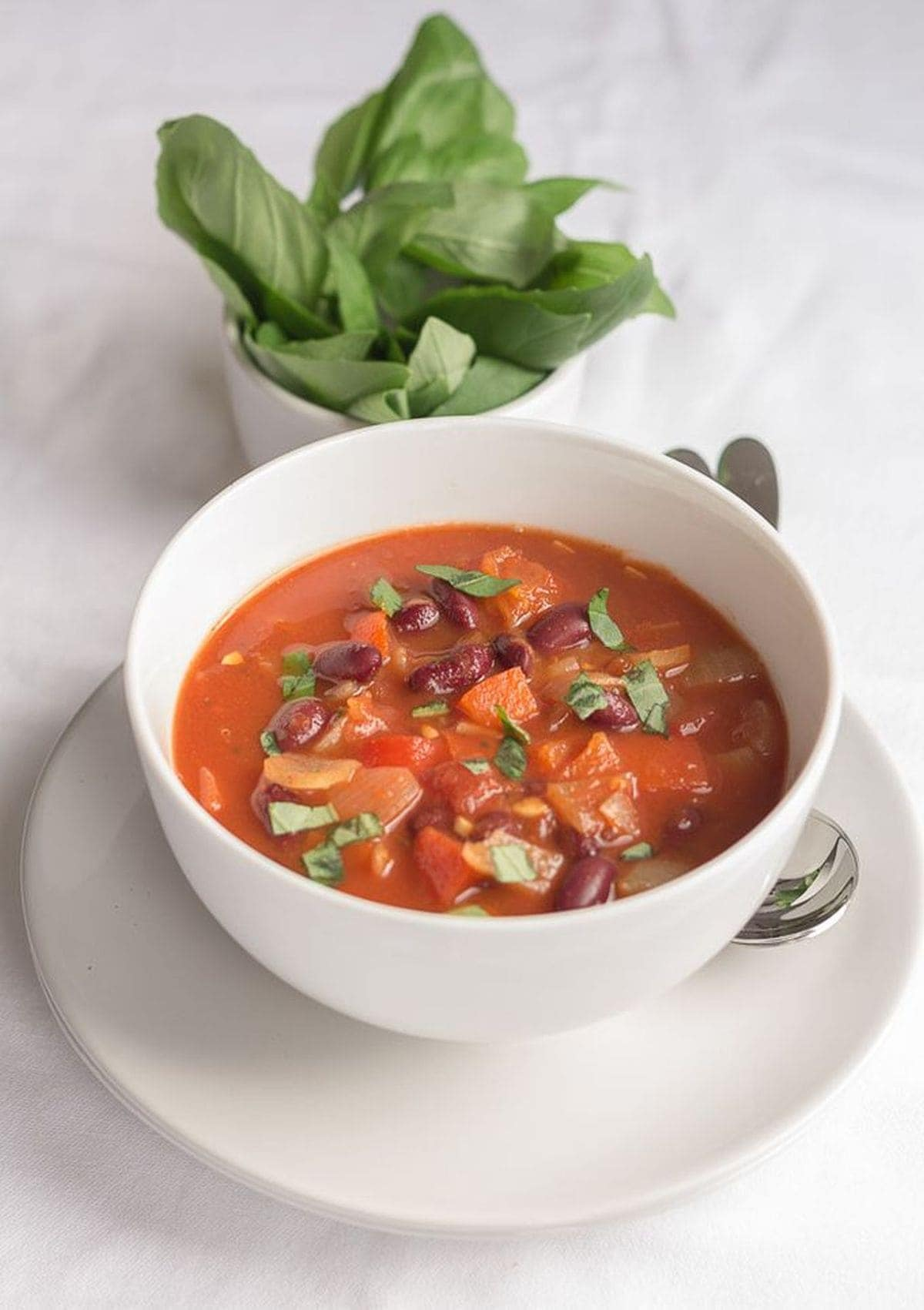 A bowl of red pepper tomato and kidney bean soup with a dish of basil leaves in the background.
