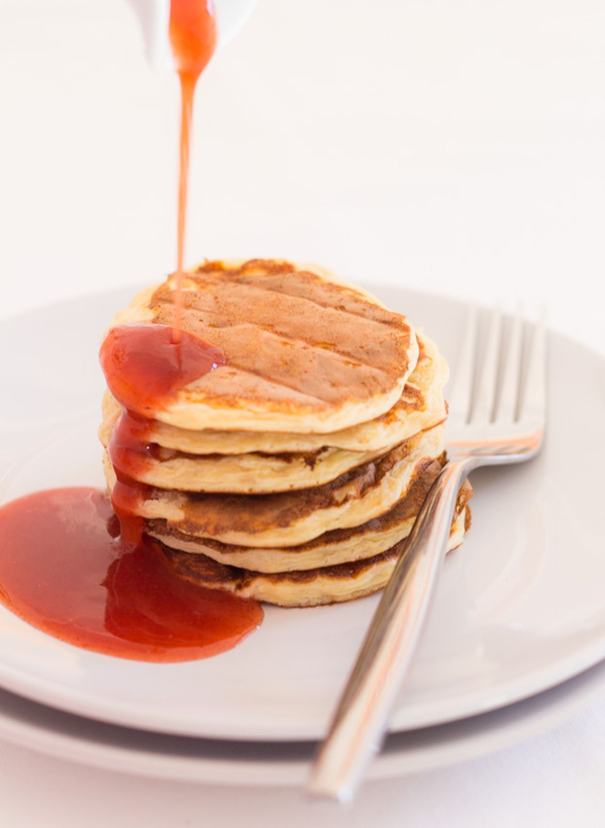 A stack of Scottish porridge oat pancakes on a plate with syrup being poured over.
