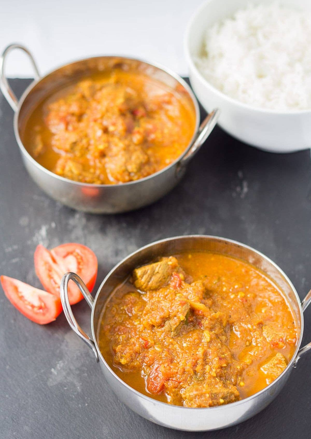 Two balti dishes of beef curry casserole with a dish of rice to the side.