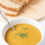 carrot and lentil soup in a bowl with sliced bread behind