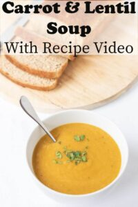 A bowl of carrot and lentil soup garnished with a spoon in it. A loaf of bread sliced on a bread board in the background. Pin title at the top.