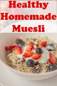 A bowl of healthy homemade muesli served with greek yogurt and chopped strawberries and blueberries.