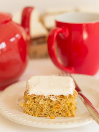 A slice of orange and apricot tray bake on a white plate with a pot of tea and cup in the background.