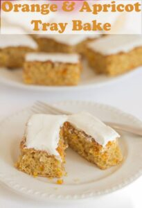 A slice of orange and apricot tray bake on a plate cut in half with a folk. Pin title at top.