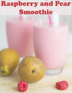 Two glasses of raspberry and pear smoothie with straws in and a decoration of pears and raspberries in front.