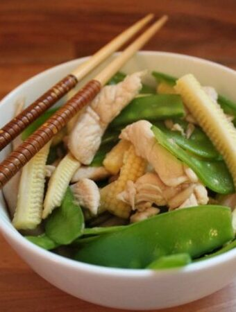 Finished bowl of stir fried chicken and corn with chopsticks on the side.