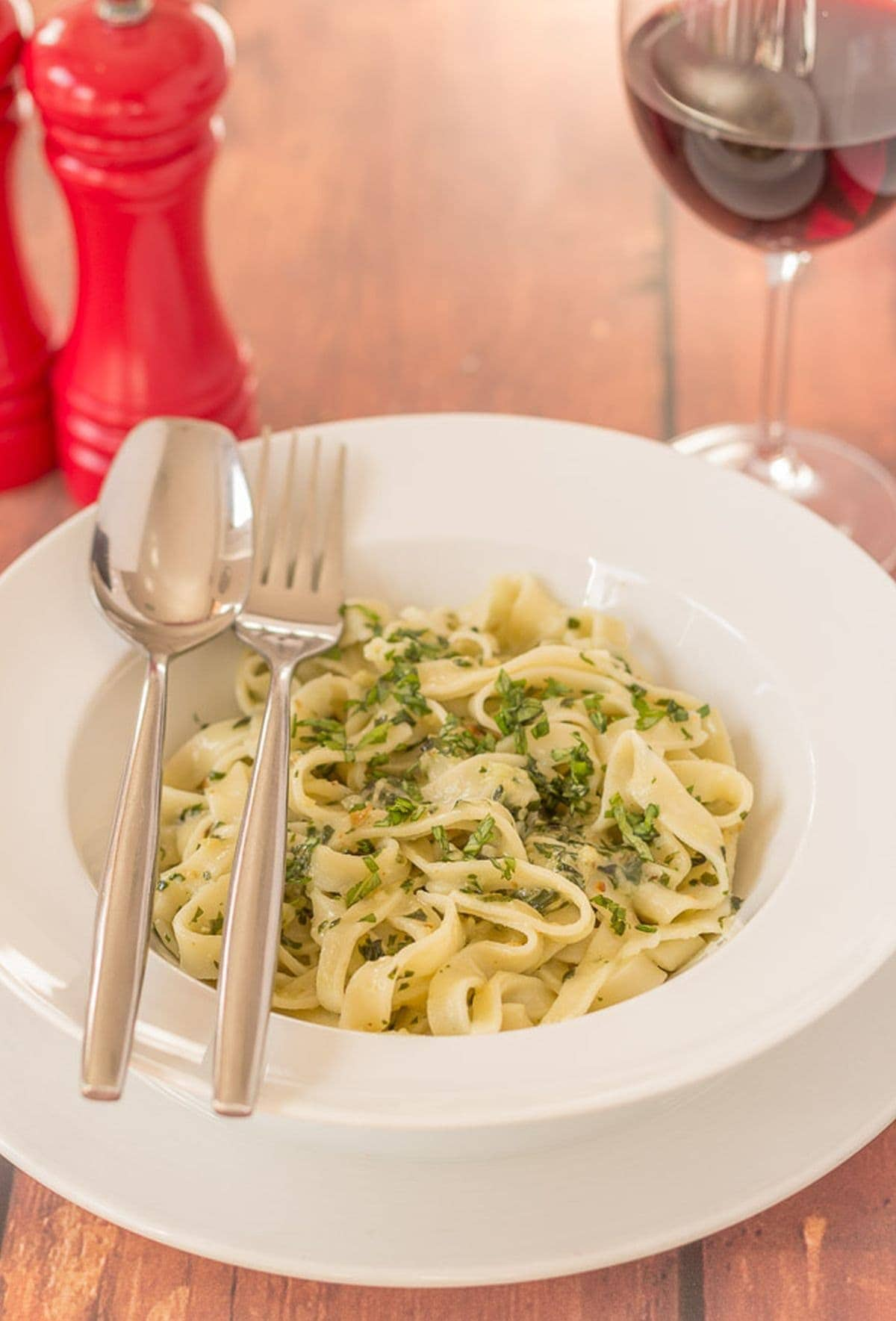 A bowl of homemade tagliatelle and pesto knife and fork to the side and a glass of red wine and salt and pepper shakers in the background.