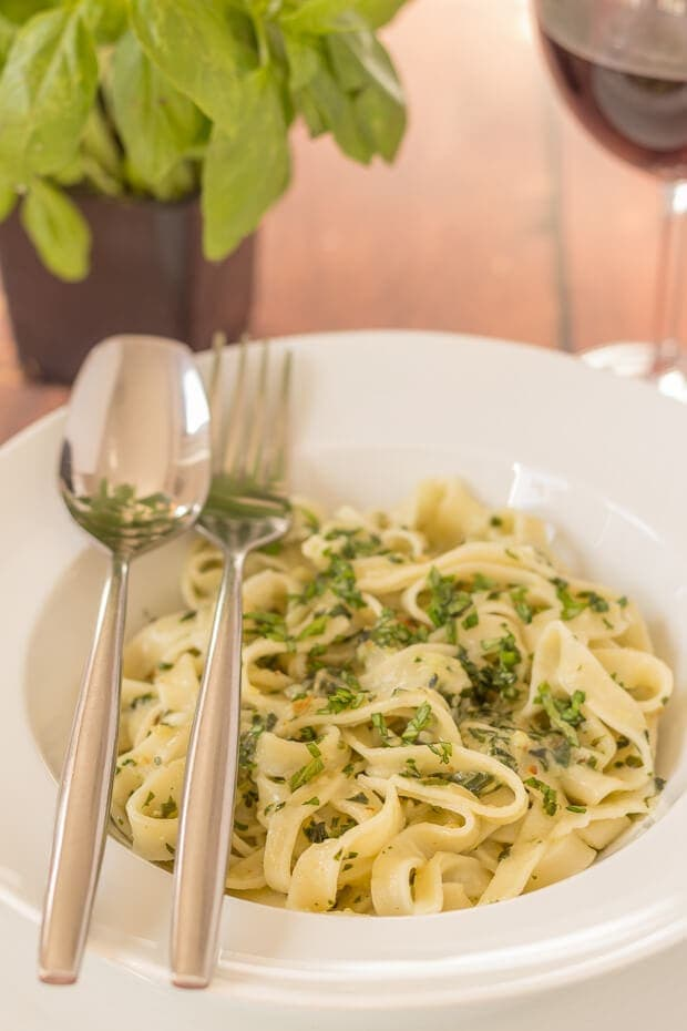 A bowl of fresh'y make tagliatelle and pesto with a glass of red wine and basil plant in the background.