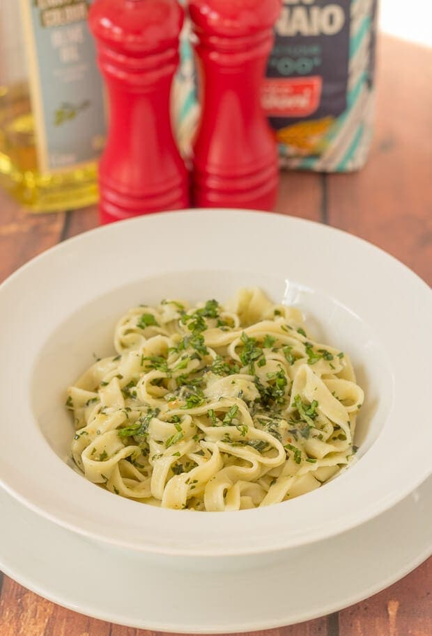 A bowl of homemade tagliatelle and home made pesto. Salt and pepper cellars and oil and pasta flour in the background.