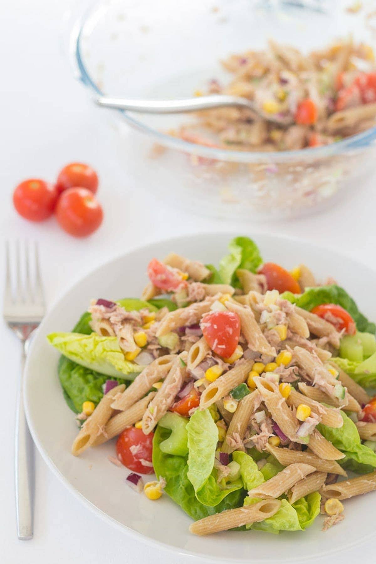 A plate of tuna and sweetcorn pasta salad with a bowl of the remainder of the pasta salad at the top.