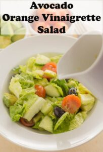 A bowl of avocado salad with a jug of orange vinaigrette being poured over. Pin title text overlay at top.