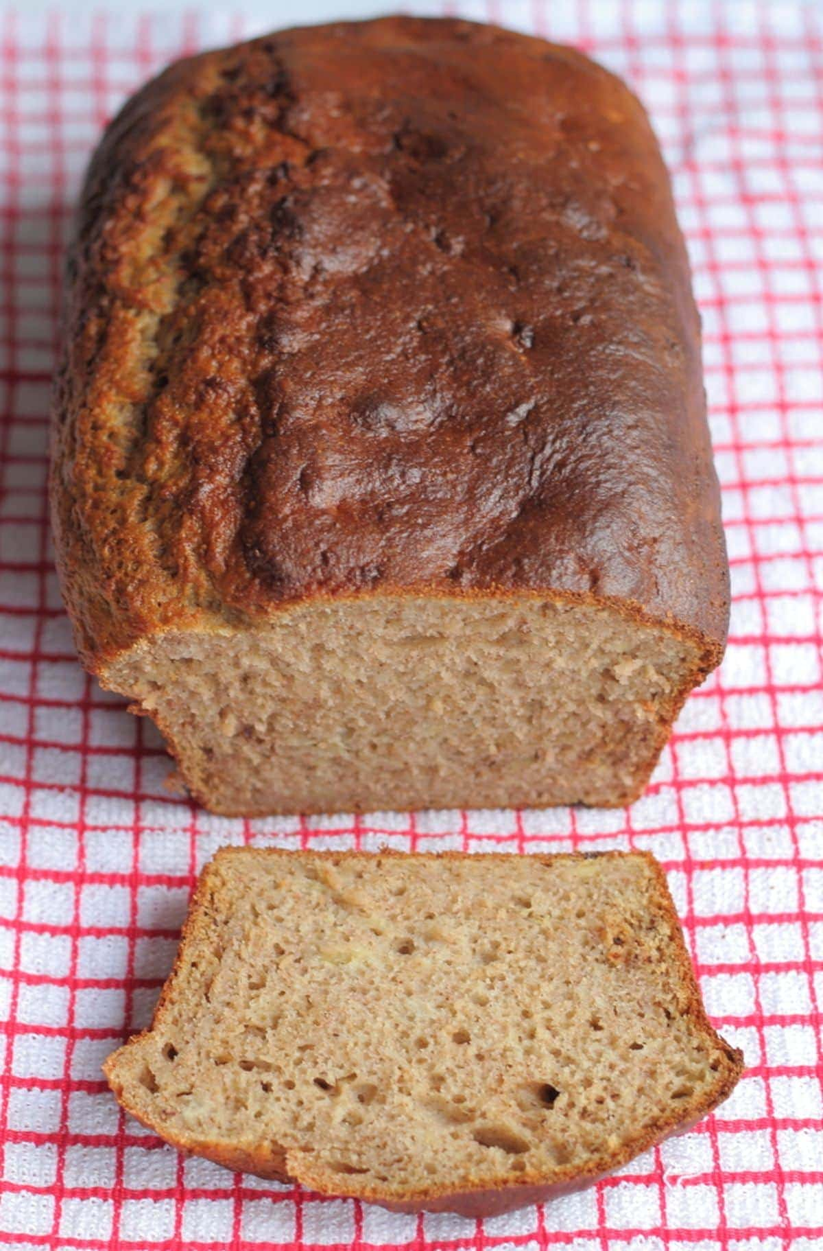 A loaf of low calorie banana bread on a tea towel with a slice front off.