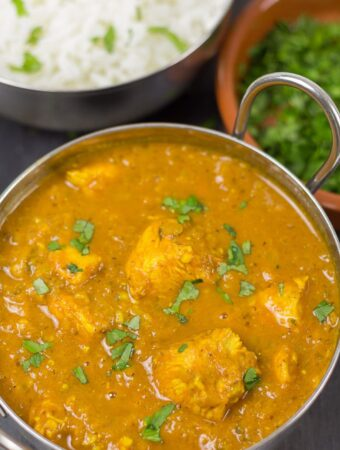 A balti dish of chicken vindaloo, garnished with chopped coriander. A rice dish and a dish of coriander in the background.