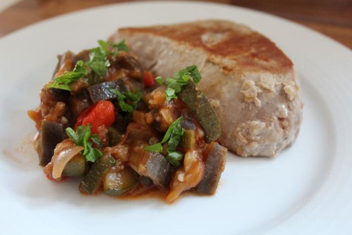 A plate of ratatouille with a thick tuna steak beside it.