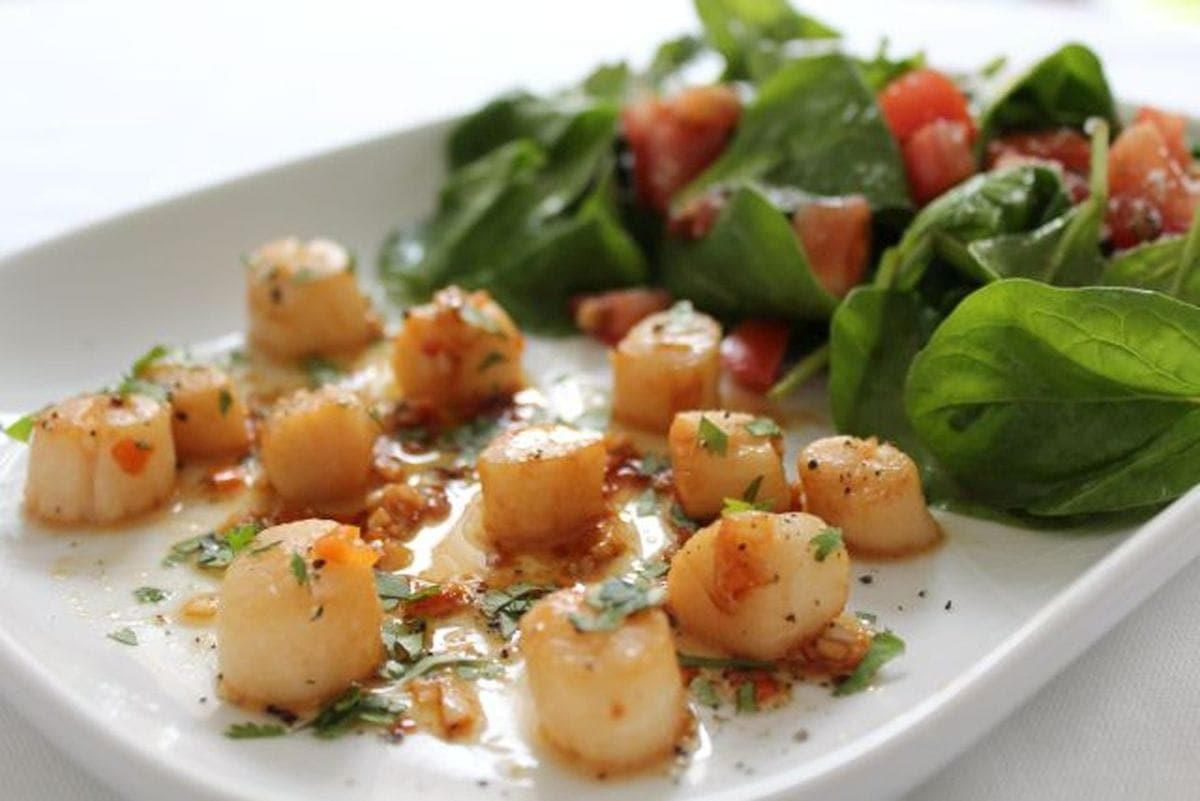 Scallops with chilli and lime served on a white plater serving dish with a spinach and toasted pine nut green salad.