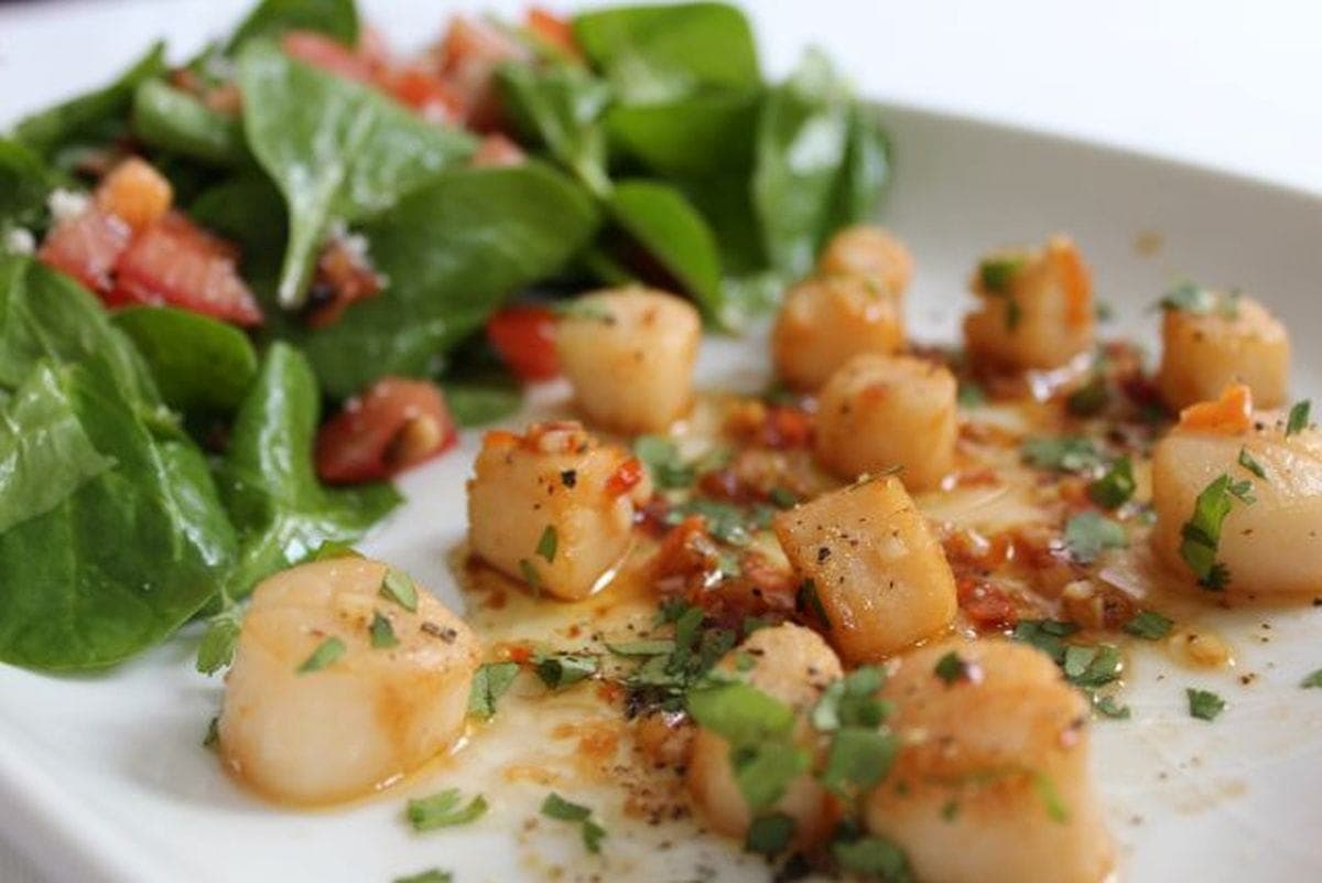 Close up of a plater dish of scallops with a chilli and lime dressing and a spinach and pine nut salad to accompany.