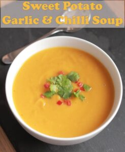 A bowl of sweet potato garlic and chilli soup garnished with chopped red chillies and coriander.