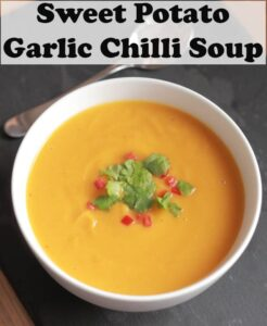 A bowl of sweet potato garlic and chilli soup garnished with coriander and chopped red pepper. Pin title text overlay at top.