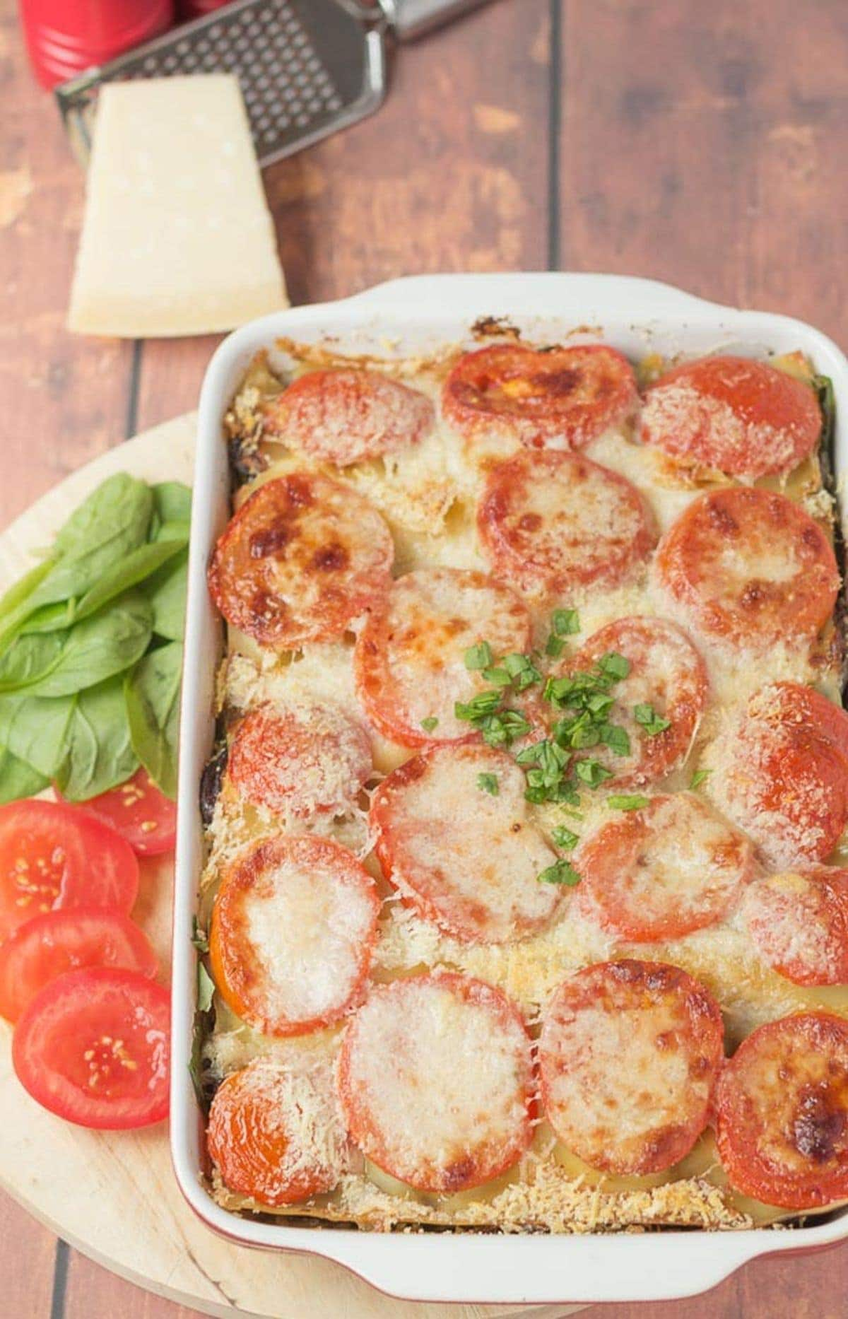 Birds eye view of a dish of vegetarian lasagne taken out of the oven and placed on a chopping board.