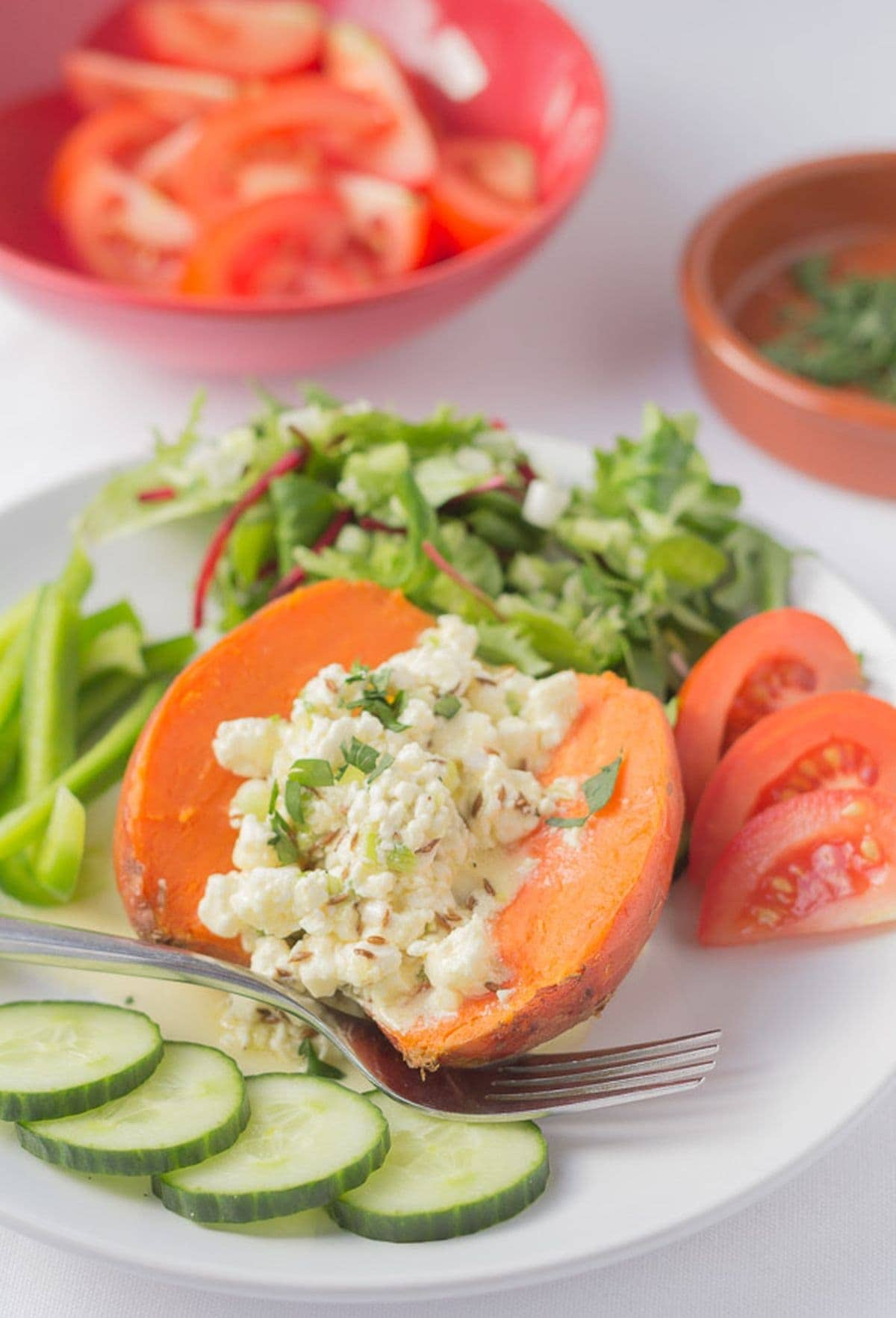 A plate with a baked sweet potato on filling with feta and orange filling and lettuce, cucumber and tomatoes around the edge of the plate.