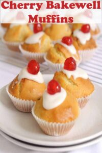 A plate of three cherry bakewell muffins with the rest of the baked muffins on a wire baking rack in the background. Pin title text overlay at top.