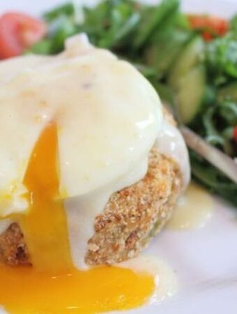 A homemade smoked haddock fish cake topped with a burst yolk poached egg and a side salad at the back of the plate.