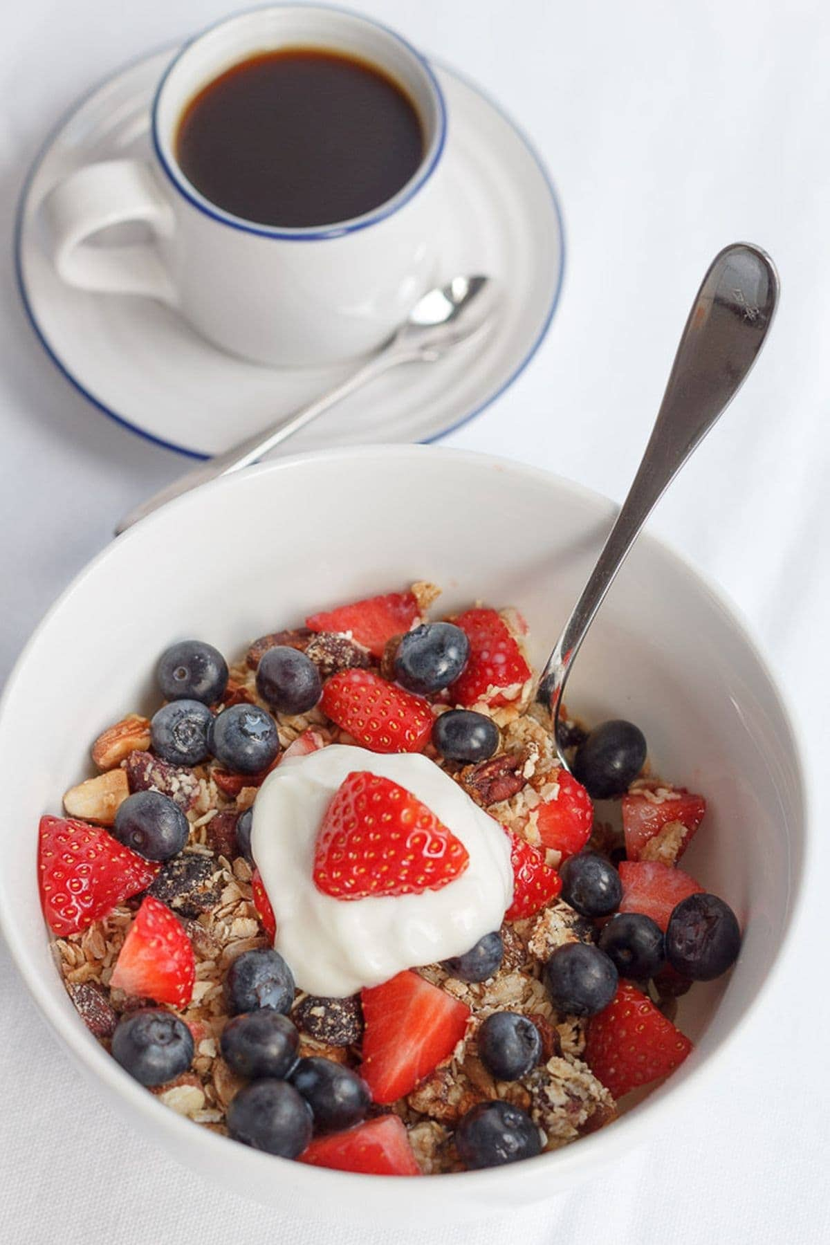 A bowl of homemade granola topped with blueberries, chopped strawberries and a dollup of yogurt. A cup of coffee to the side.